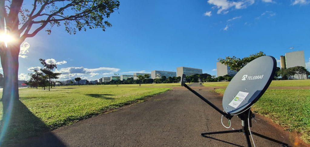 Antena da Telebras em frente aos Ministérios. Gramado verde ao fundo, céu azul e a sombra de uma árvore na lateral da imagem.